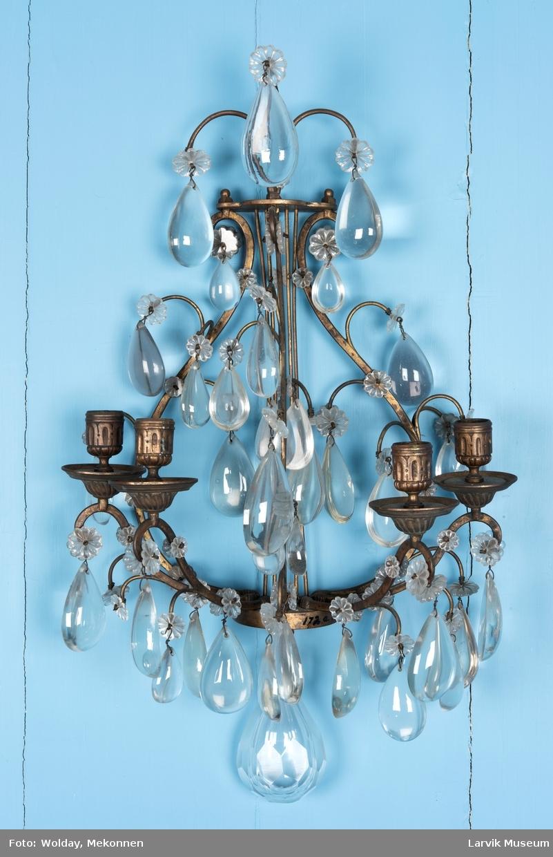 Lyreformet med 4 lyseholdere. Dråpeform. Prismer festet ved blomster i krystall