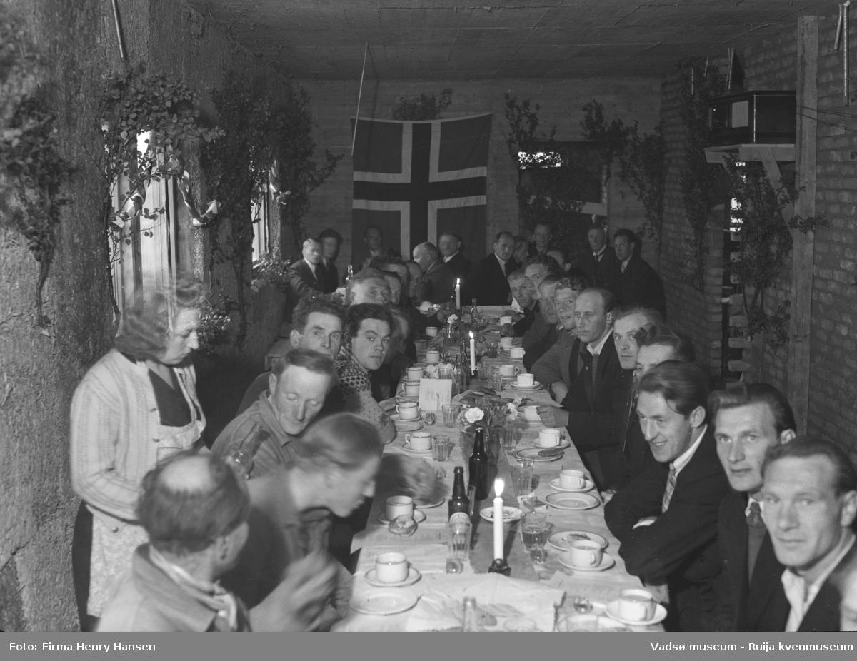 Bildet viser kranselaget på Finnmark Kringkaster i august 1948. Vi ser et langbord dekket med flasker og glass, en kvinne til venstre skjenker fra en flaske, på begge sider av bordet sitter 28 menn, mange er festkledd med dress og slips. Rommet er smalt, bordet med stolrekke på begge sider og ved kortenden dekker bordbredden rommet. På veggen til venstre er det to vinduer. Rommet er pyntet med løv og norske flagg, et stort flagg på kortveggen. På veggen til høyre står en radio på en liten hylle.