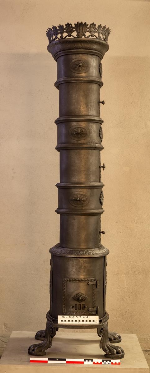 """Fire etasjes oval ovn i biedermeier stil. Ovnen står på fire """"dyreføtter"""". Ovnsdøren er plassert på kortsiden. Over brennkammeret er det i hver etasje gjennombrutte mønstrede dører. Ovnen avsluttes med en krans på toppen. Ovnen har store glatte flater og er dekorert med rosetter og palmetter. Ovnen er merket med verkets navn på brennkammerets bakplate."""