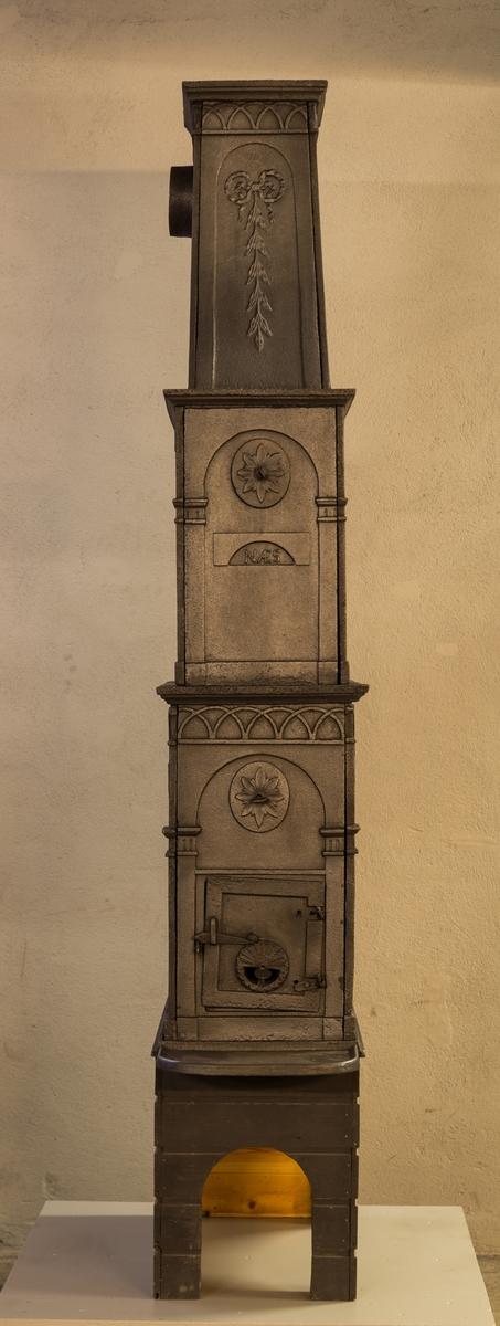 """Ovn i 3 etasjer med ovnsluke på kortside og røykuttak på siden i 3. etg. Eksemplaret er som avbildet i 1809 katalogen. Med lave relieffer. Langside 1. etg - Kentaur mot høyre i buefelt oppå en sokkel. Klubb i høyre hånd, pels over venstre skulder. Girlande over, hengende i volutter som avslutter hjørne pilastrer. Vifteformet motiv ved voluttene. Pilastre ved hvert hjørne, både ved Langside og Kortside. Felt med overlappene halvsirkler øverst, også både ved Ls og Ks. Både 2. og 3. etg har gjennomgående buet åpning på langsidene. Toppetasjen """"løftes opp"""" med en svai i formen."""