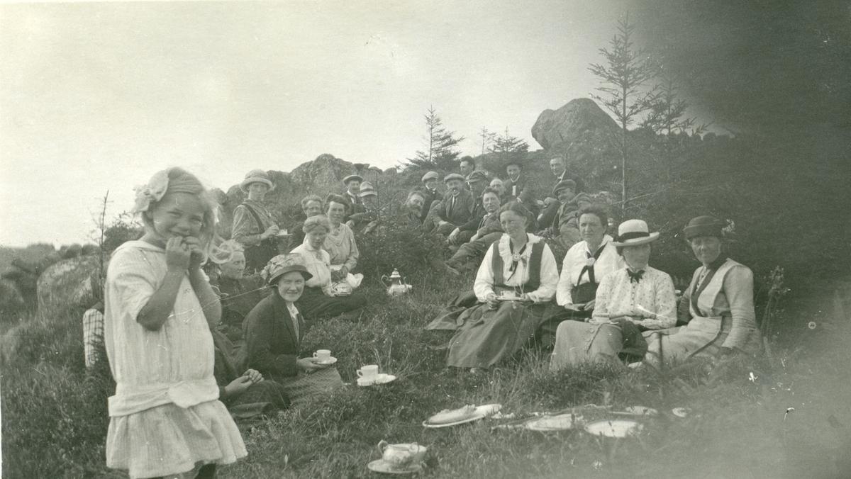 Postkort med en gruppe kvinner, barn og menn har matpause ute i naturen, i forbindelse med besøk hos Arne Garborg, Knudaheio, Time kommune. Dette var i 1916.