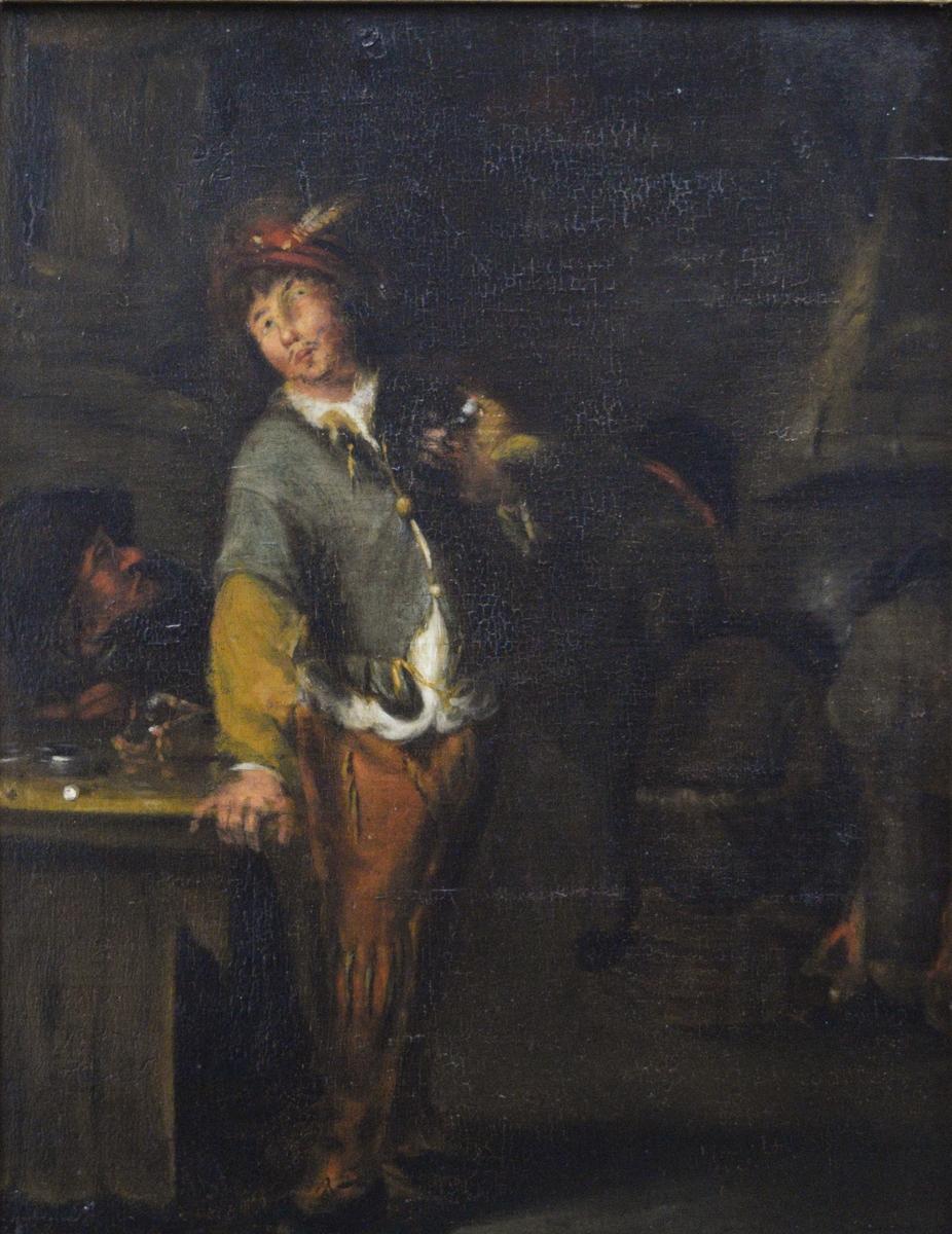 Mannsfigur. Bildet viser en ung mann som støtter seg med den høyre hånden til en bordplate. På venstre arm holder han en fugl, kanskje en papegøye. Ved bordet helt til venstre i bildet sitter en kvinne (?) med svart hette over hodet. Hun bøyer seg frem og snakker til mannen bakfra. På bordet ligger forskjellige mindre gjenstander. Over kvinnen skimtes et vindu. Til venstre i bildet sees så vidt tre personer foran en peis eller grue.