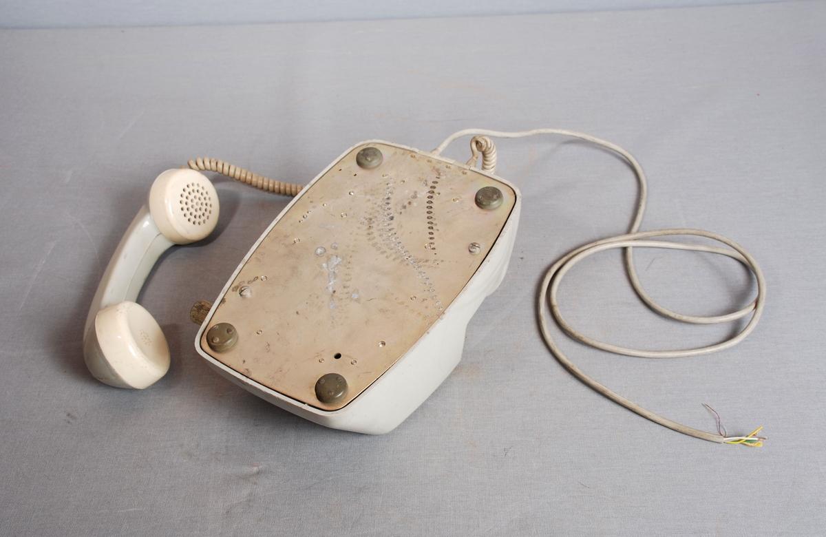Telefonapparat for intern bruk. Sveiv på høyre side. Firkantet plastfelt på fronten. Telefonrør på dobbel gaffel montert til apparatet med spiraltvunnet gummiert ledning. Ledning til støpsel montert i bakkant.