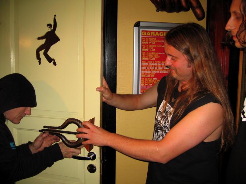 Dennis Reksten og Grutle Kjellson monterer Spellemannpris fra Enslaved som nytt do-dør-håndtak på Garage.