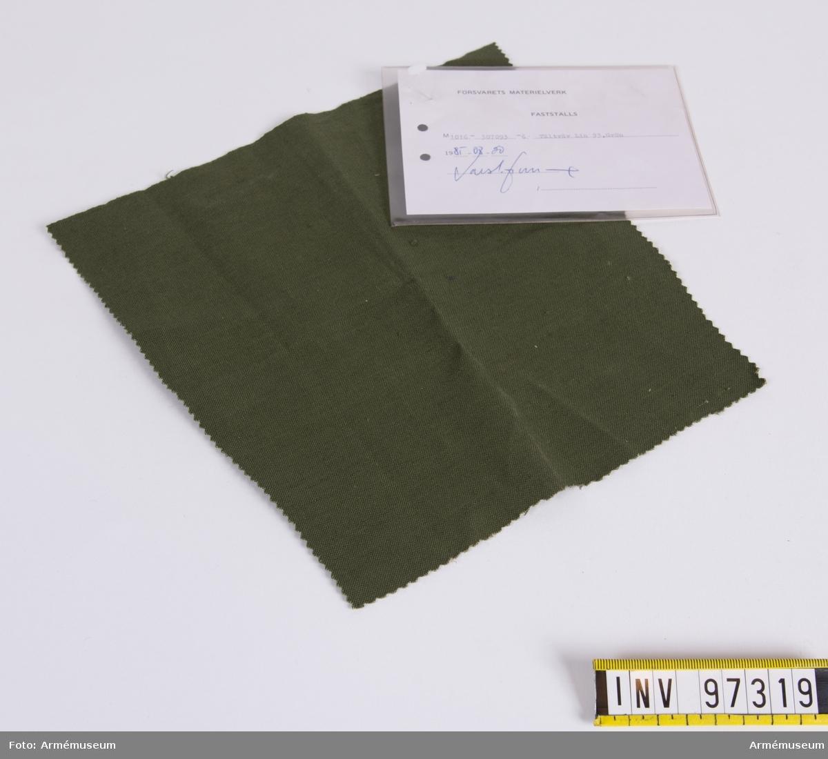 """Vidhängande modellapp med text: """"Försvarets materielverk. Fastställs. M 1016-307093-6 Tältväv Lin 93, Grön. 1985-08-20 (oläslig sign)"""""""