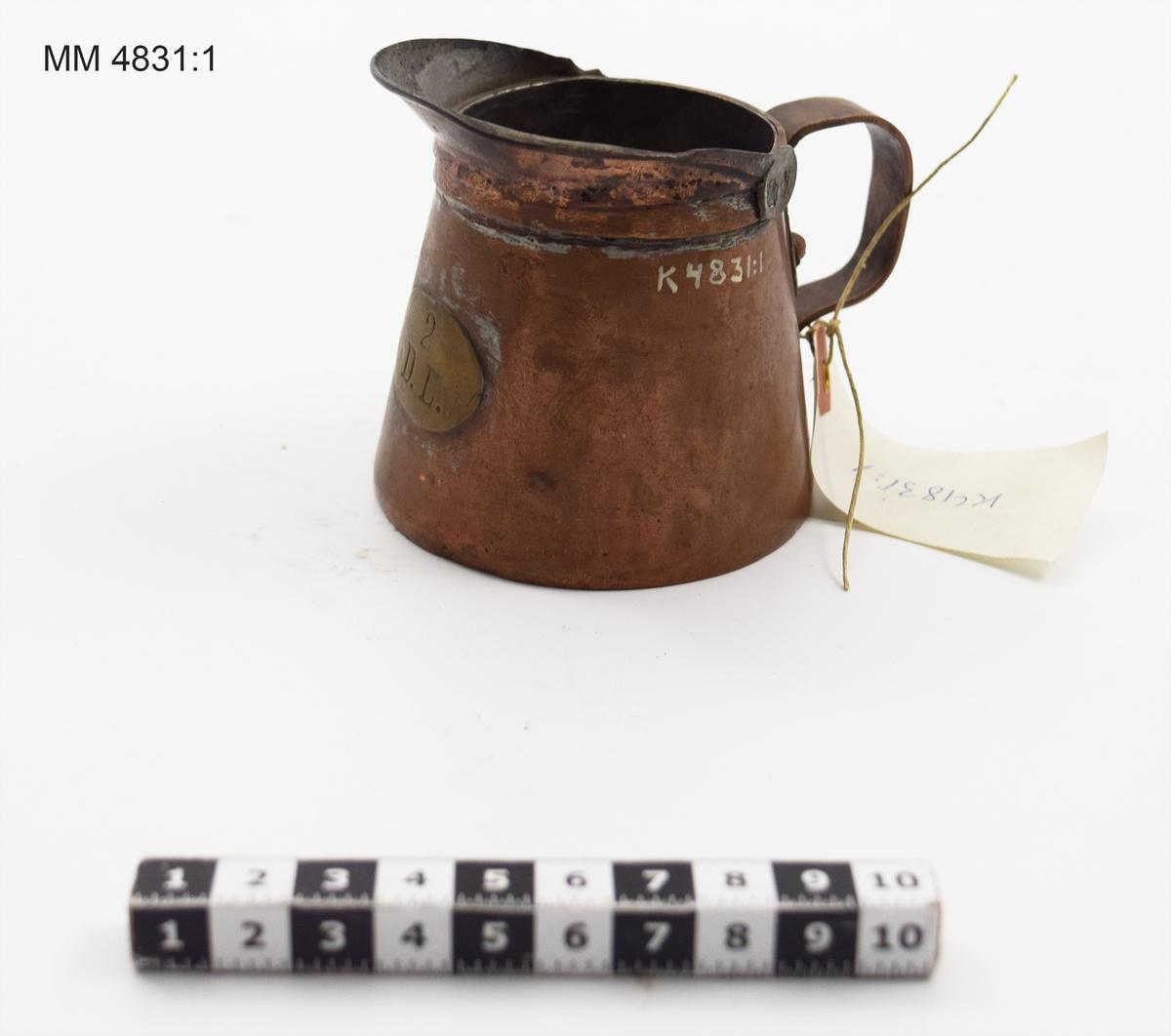 """Målkärl om 2 dl av koppar, cylindriskt. Märkt på mässingsplåt med """"2 D.L."""" samt med tre kronstämplar och två kröningsstämplar, den ena med årtal 48 och den andra med K."""