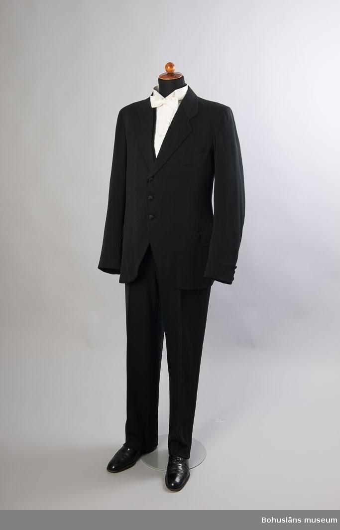 Svart väst, knäppes med sex klädda knappar med mönstrat tyg. Två infällda fickor och en dito bröstficka. I ryggen slits och spänne för att reglera vidden. Ryggen av svart merciserad bomull. Fodrad med vit bomull med svarta ränder. Sammanhör med brudgumsklädsel se UM026632. Personuppgifter om brukaren och bröllopet se UM026632