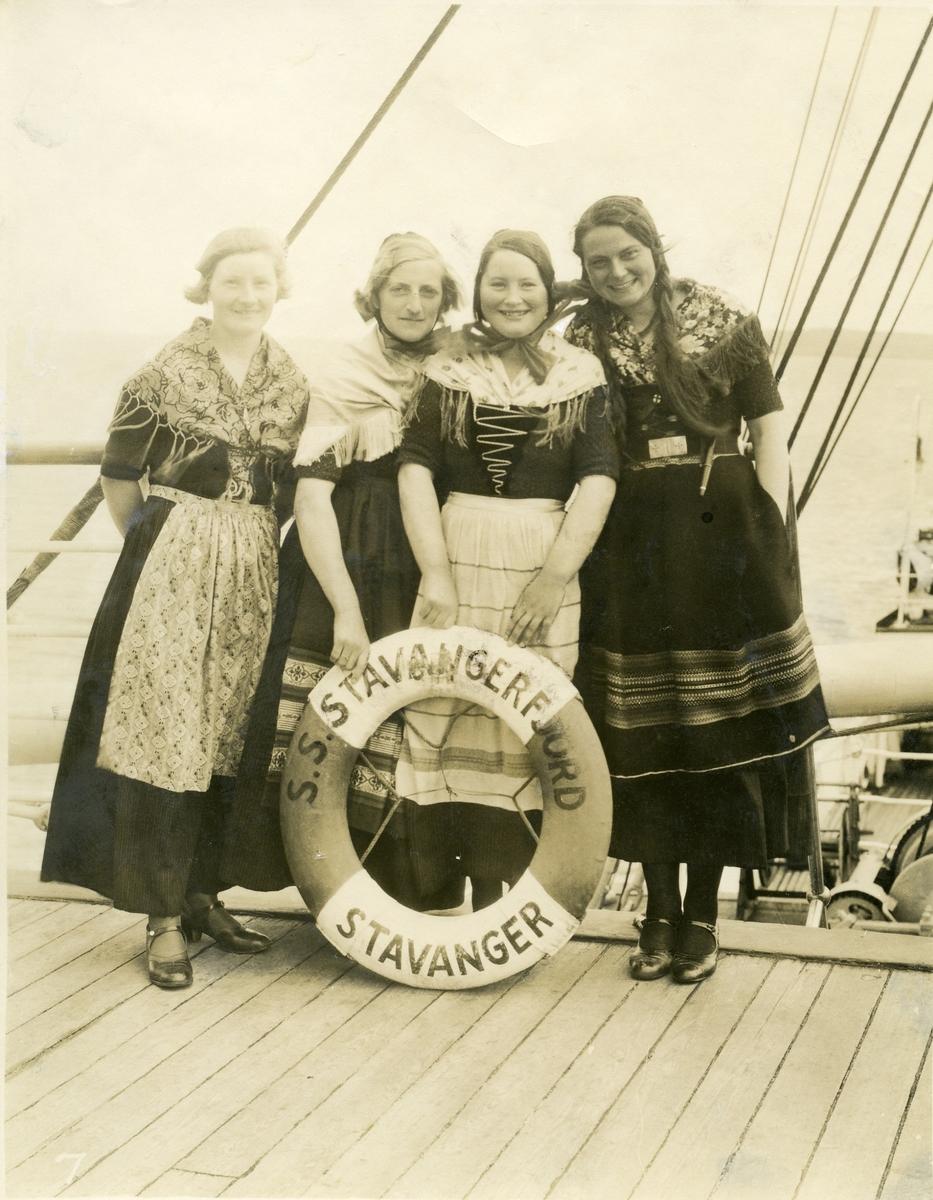 Fire kvinner kledd i folkedrakt, på dekk av S/S Stavangerfjord i Torshavn, Færøyene.