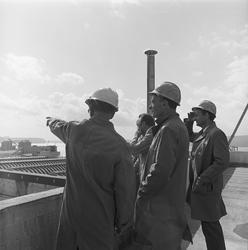 Tre menn ser utover fabrikkområdet på Herøya.