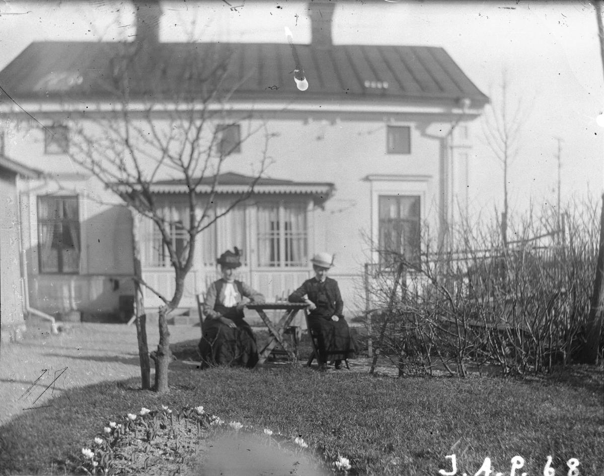 """""""Stora huset Kryddgårdsgatan 32 B, Sandgatan 28"""". Två kvinnor framför det hus som var familjen Johan August Petterssons hem fr.o.m. 1913 och framåt, Enköping. Vy från nordväst."""