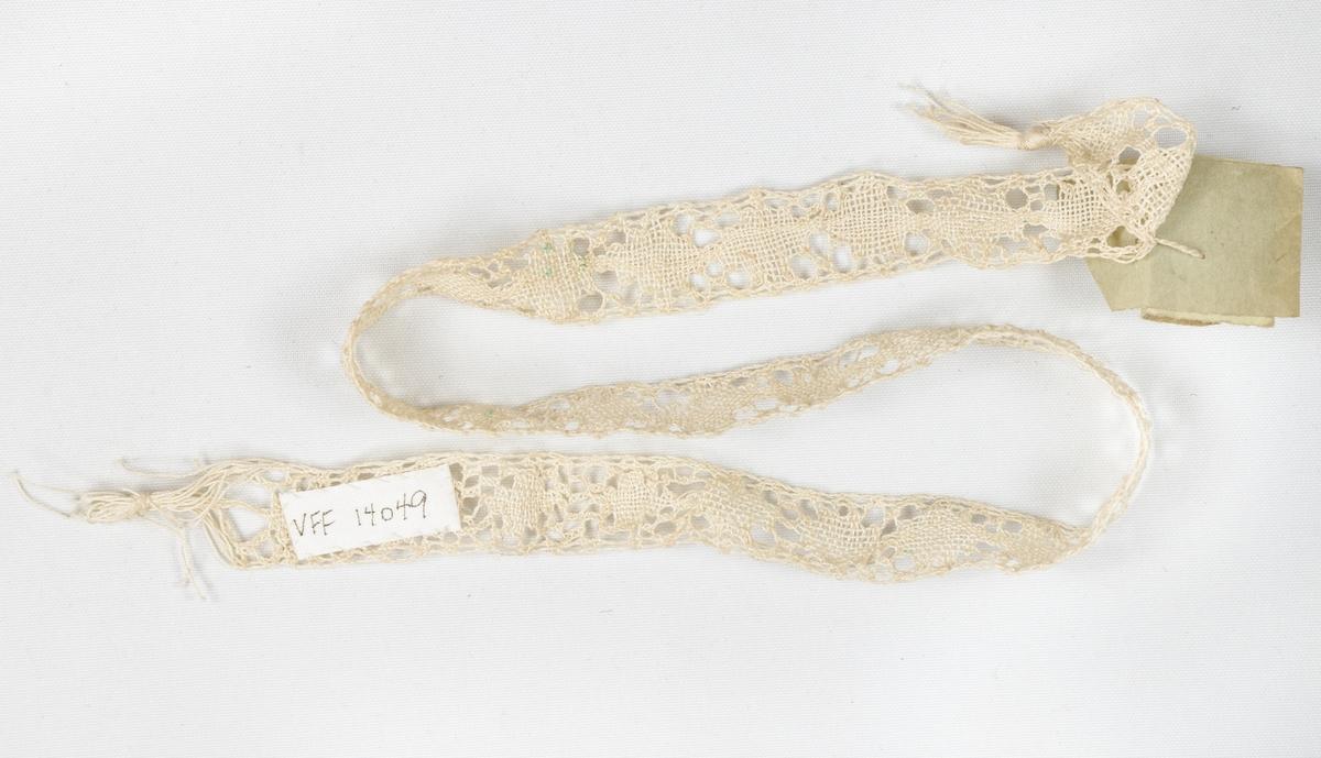 Selskapshansker (a+b) i hvitt tynt skinn. 12 cm lang splitt nederst i håndleddet, med tre hvite små knapper.