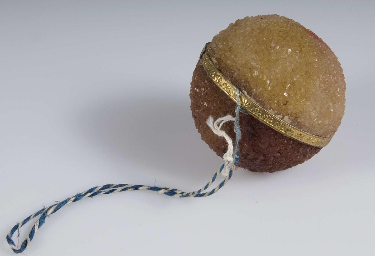 Boll av sockermassa i olika ljusa färger, guldband runt magen. Upphägningssnodd.Sammanhörande med konfekt UM16808-UM16832.
