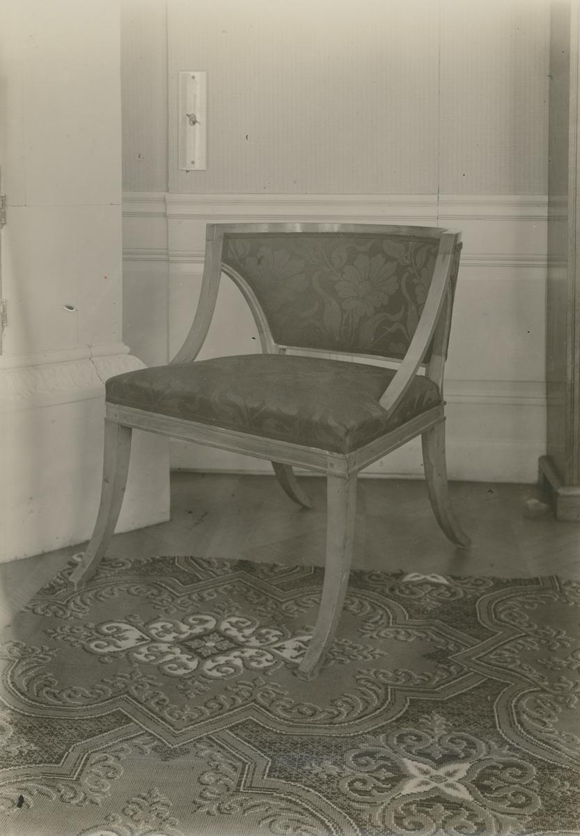 Blekhems herrgård, biblioteket. Länstol av ljust trä med slät struktur, polerad.  Klädsel rött ylle och band. Ursprungligen från Blekhem.