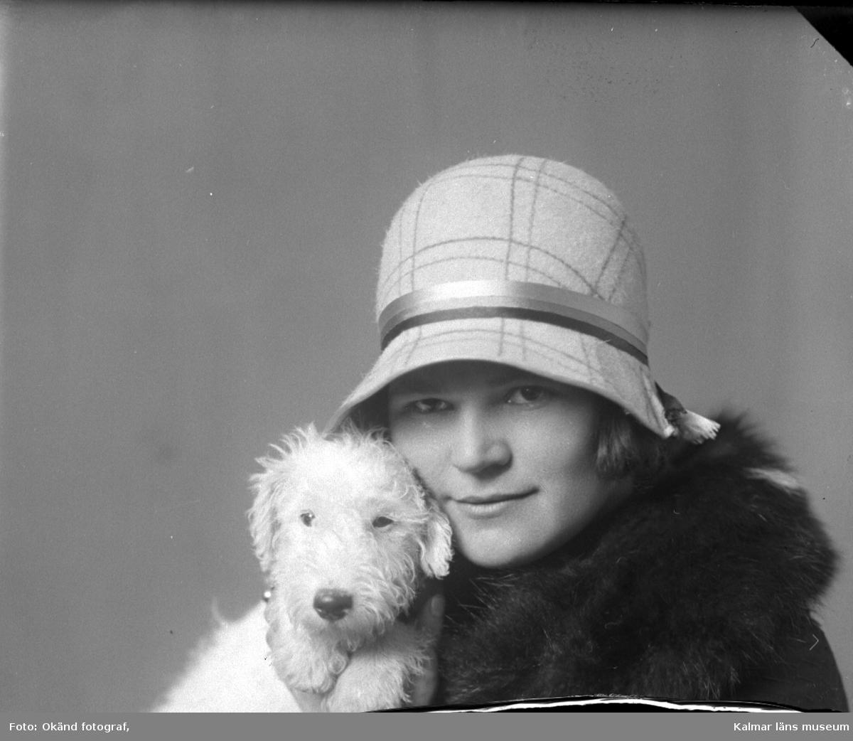 En kvinna i hatt och päls med en hund med koppling till Hirschs Pianomagasin.