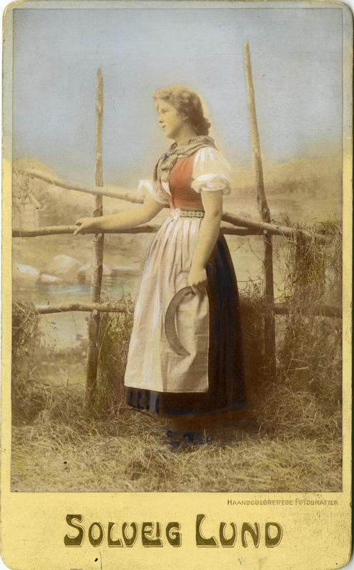 Kolorert studiofotografi av kvinne med sigd og høyhesje. 1906. (Foto/Photo)