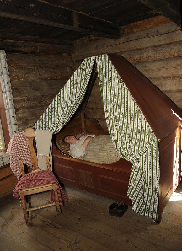 Jente ligger i himmelseng og sover med hendene pent oppå dyna. Skoene står under senga, og klærne henger på en stol ved siden av senga.