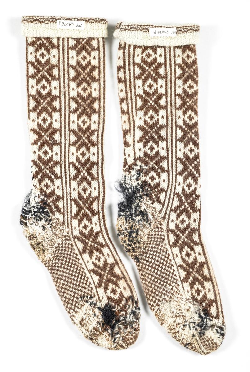 Strømpe, A og B, heimestrikka strømpe i kvit og sauesvart ullgarn. Stoppet  mange plassar i foten og hælen.