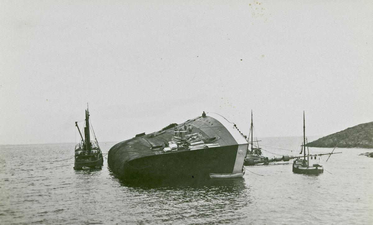 Havarist. Større skip ligger på siden med flere mindre båter rundt. Mennesker og materialler på siden av skipet.