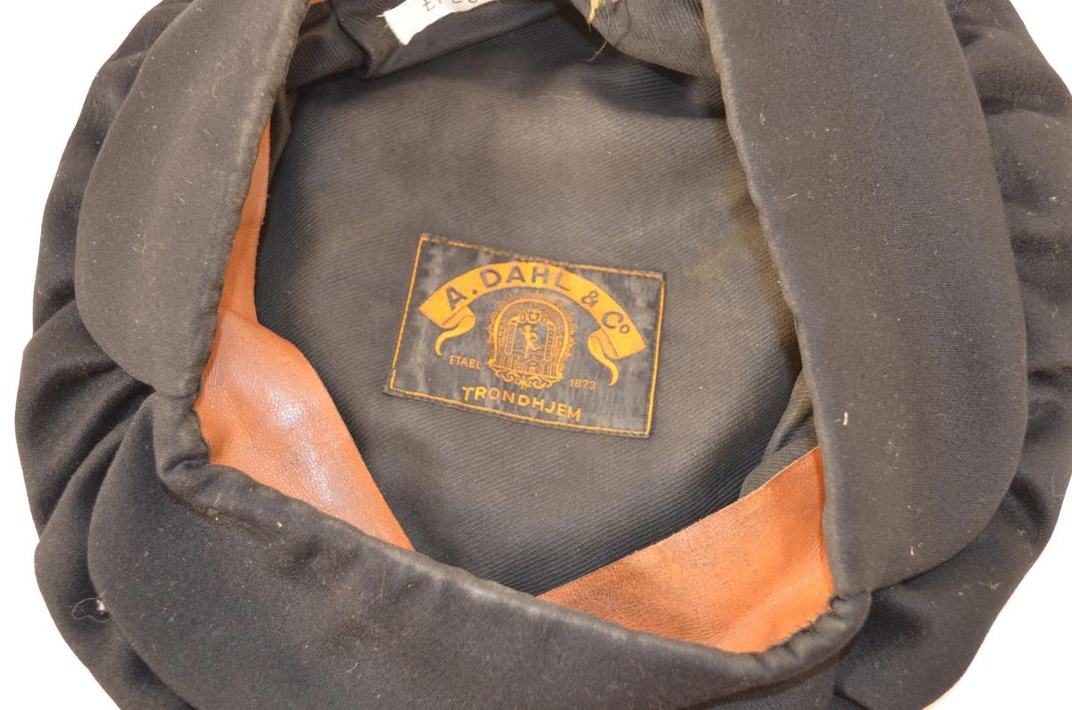 Lue i svart klede. Oppbretta kant fòra med skinn inne i lua. Faldelagt pull.