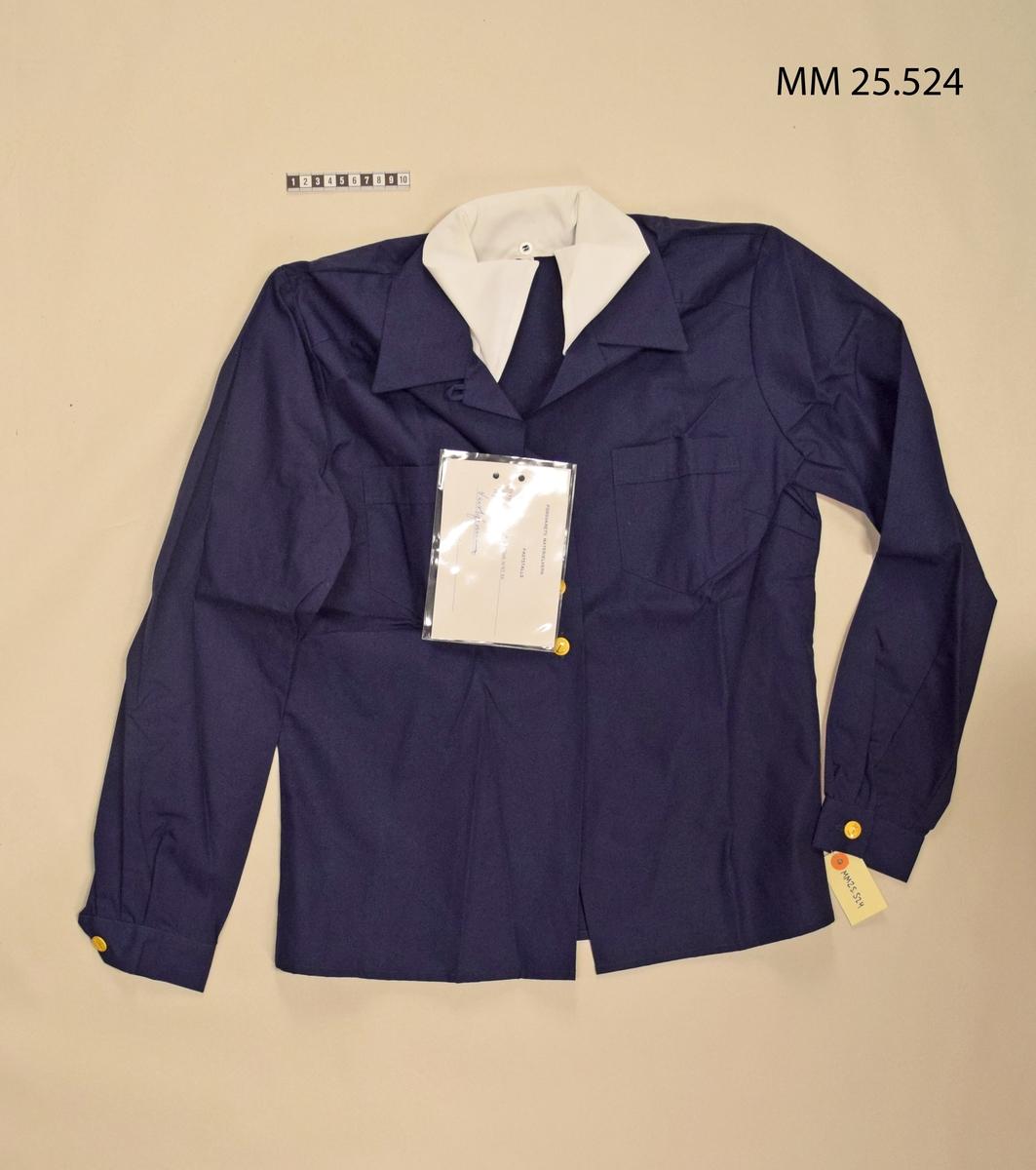 Mörkblå klänning med löstagbar vit krage. Bröstfickor på båda sidor. Knäpps med fyra guldknappar med ankare. Manschetter knäpps med likadan knappar. Vidhängd lapp ger information om fastställandet.