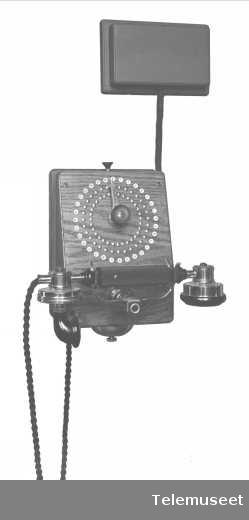 Telefonapparat, lokalt veggapparat i tre. Med mtlf.liggende. Klokke likestrøm. Elektrisk Bureau.