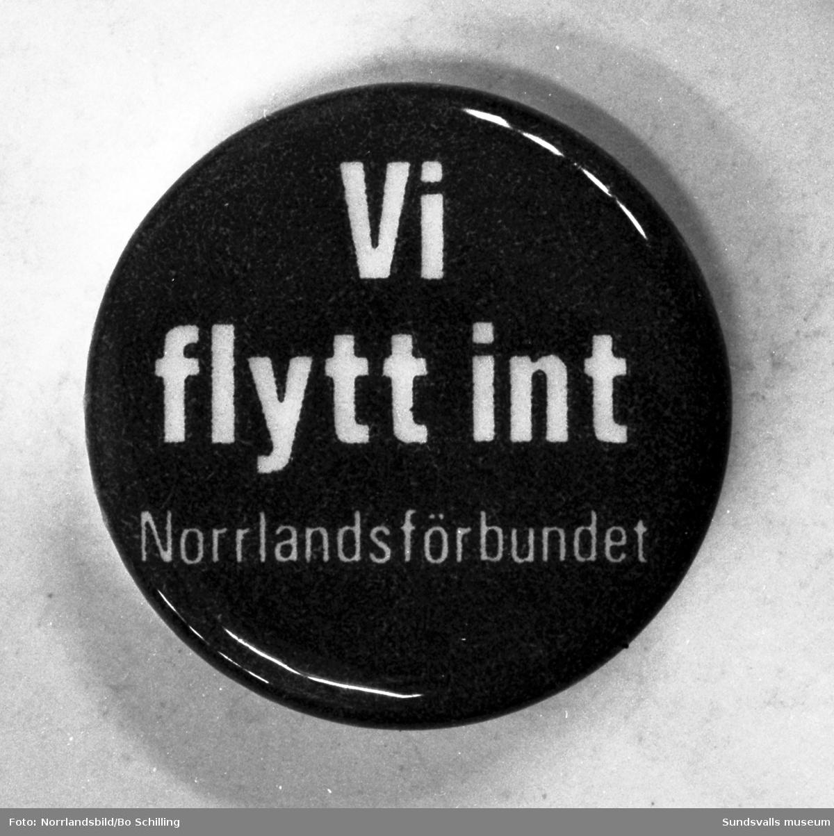 """Norrlandsförbundets märke med texten: """"Vi flytt int""""."""
