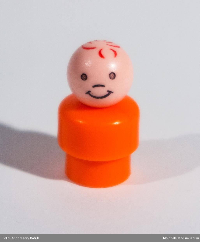 """Rund, orange plastfigur tillhörande Fisher-Pricegarage från 1970-talet. """"Kroppen"""" består av två delar varav den nedersta är smalare för att passa ihop med tillhörande leksaksbil. Ihålig underifrån och längst in är """"huvudet"""" fastskruvat. """"Huvudet"""" består av en plastkula som är målad med hår, ögon, näsa och mun. Inköpt 2001 på Second Hand av givaren, vars barn har lekt med det."""