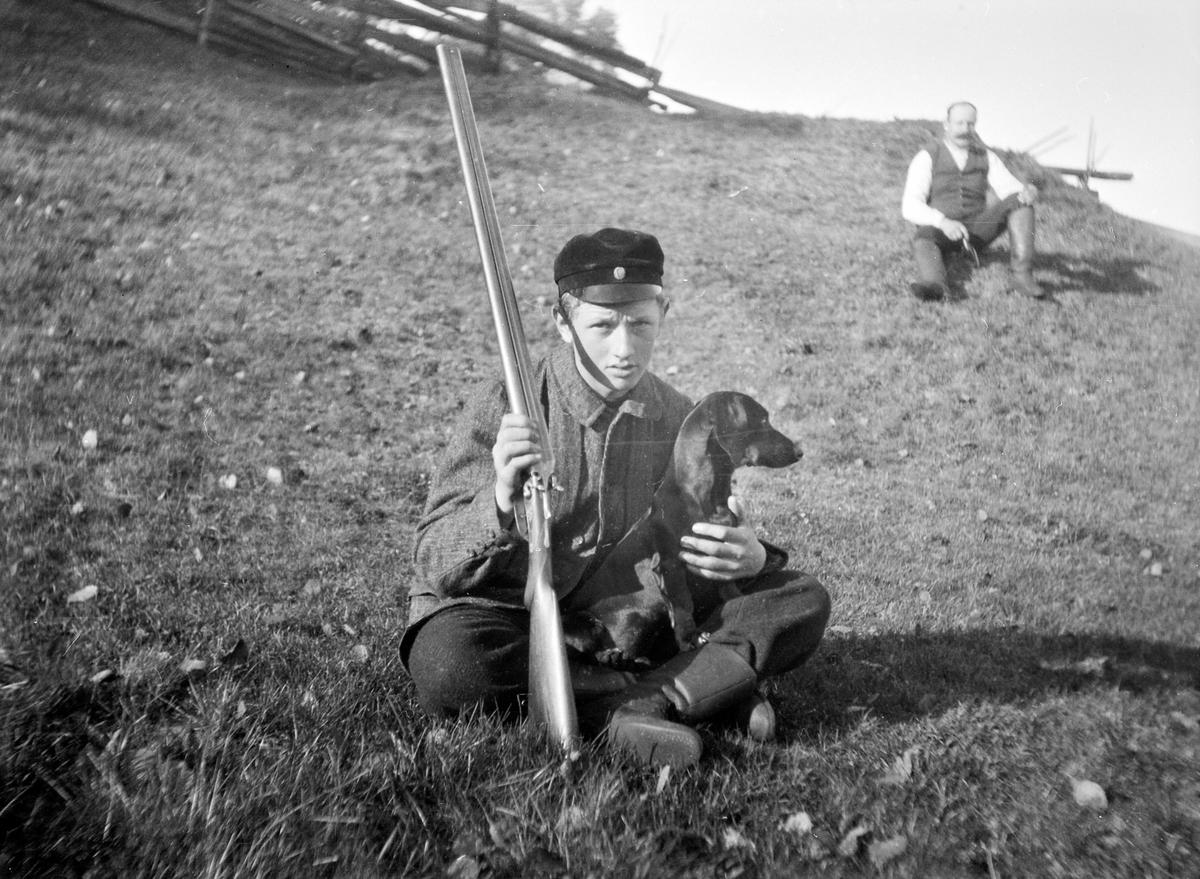 En ung jägare, troligen Ernst Bauer, sitter med en hund på en grässluttning.