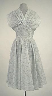 Klänning av tunt vitt syntettyg (ev polyamid) med tryckt mönster i vitt och ljusblått. Sydd av givaren efter samma mönster (invnr 106171) som klänning 106159, men med små förändringar i tillskärningen. Blixtlås i vänster sidsöm.