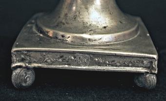 Ljusstake av tenn. Kvadratisk fotplatta med kulor i hörnen. Skaftet balusterformat. Ljushållare med godronnering.