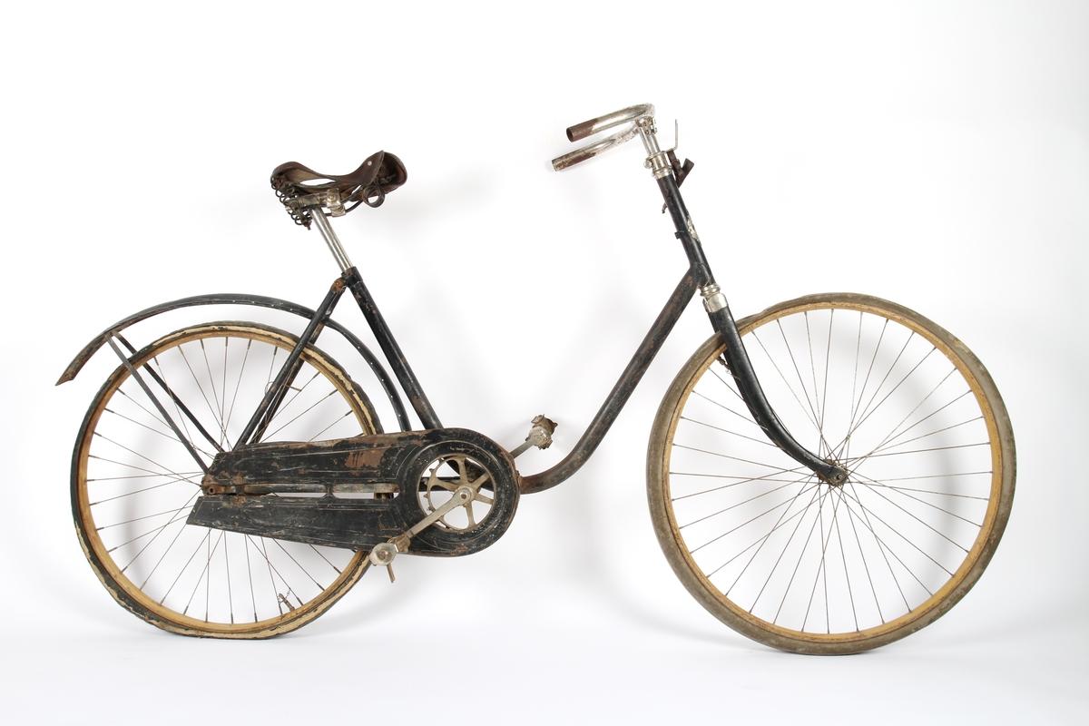 Svartlakkert damesykkel. Hjulene har stålfelger som er ådret for se ut som trefelger. Hjulene er konstruert i klassisk tre-kryss mønster, hvor krysset i framhjulet er surret sammen og loddet. Kjeden er av gammel type, hvor tannhjulene kun griper inn i annet hvert ledd. Sykkelen har Torpedo baknav med innebygd trommelbrems.