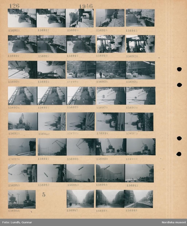 Motiv: (ingen anteckning) ; Ett fartyg i en hamn, män arbetar i en hamn, män arbetar med pappersrullar, lastkranar i en hamn, lastning av järnvägsvagnar.  Motiv: (ingen anteckning) ; Snötäckt stadsvy med fotgängare - cyklar och bilar.