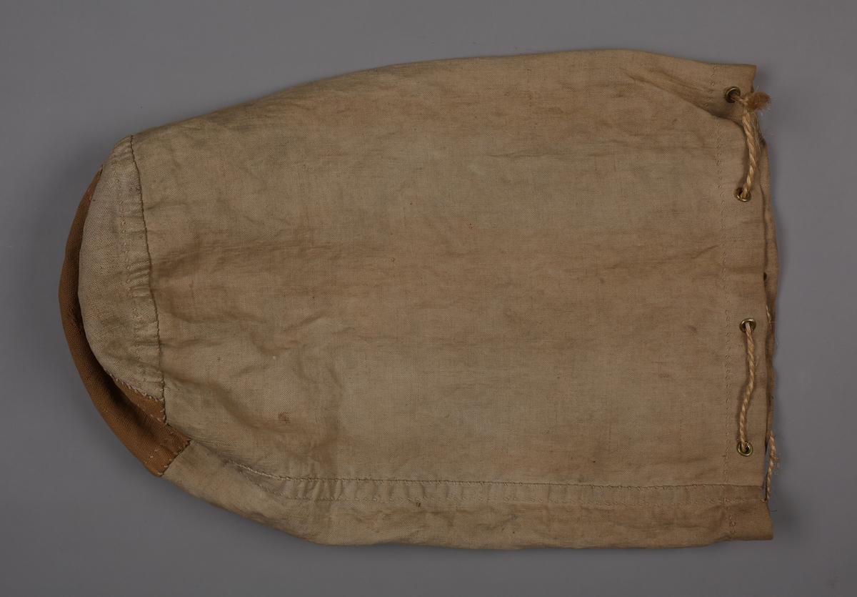 Sylinderformet skipssekk av seilduk med 8 messingringer til hull for snøring. Sekken er håndsydd og har grovere stoff i bunnen. Hampetau for snøring.