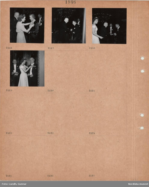 Motiv: Högtidsklädda män och kvinnor, en kvinna fäster en rosett på en annan kvinna, två män skakar hand, en kvinna och tre män, en kvinna rättar till ordensband på en man.