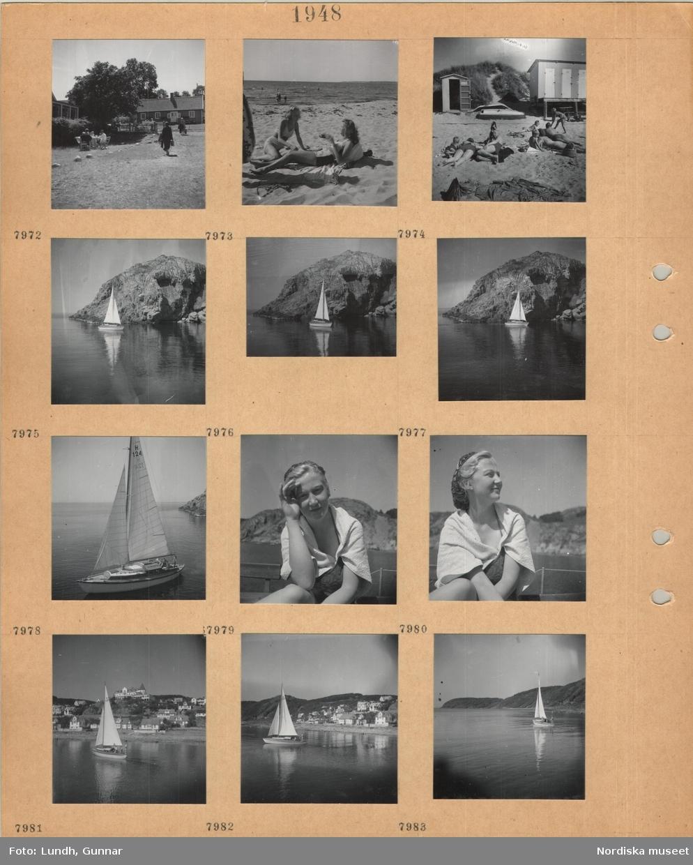 Motiv: En grupp personer sitter runt ett trädgårdsbord, småhusbebyggelse, unga kvinnor i baddräkt ligger på en sandstrand, män, kvinnor och barn ligger på en sandstrand, badhytter, segelbåt vid klippa, ung kvinna i baddräkt med handduk över axlarna, villabebyggelse i sluttning vid kust.