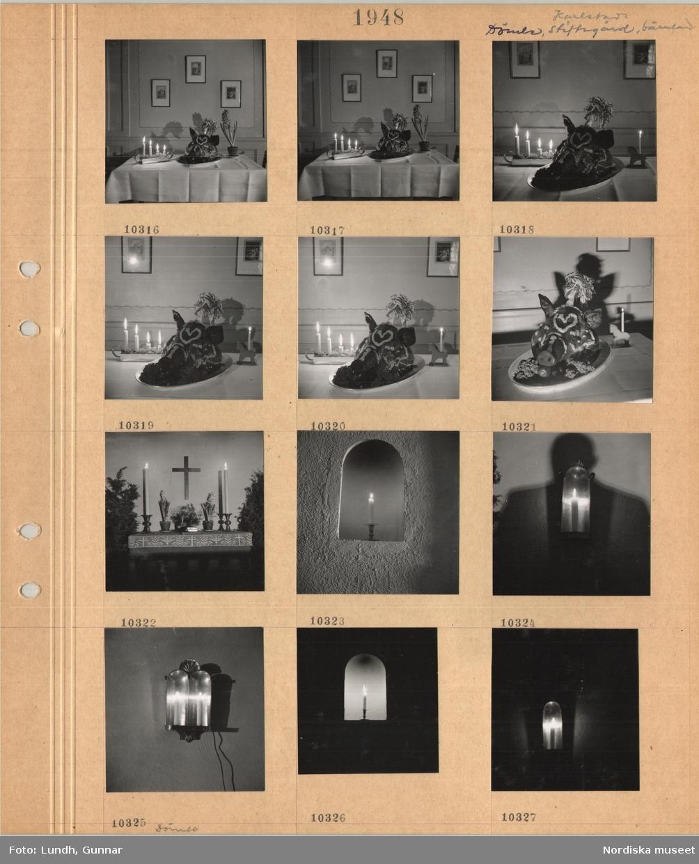 Motiv: Karlstad, Dömle stiftsgård, Värmland, bord med vit duk med adventsljusstake med fyra tända ljus, dekorerat grishuvud, kruka med hyacint, ljusstake i form av en häst, enkelt altare med ljusstakar, hyacinter, kors på väggen, väggnisch med ljusstake med tänt ljus, lykta med tänt ljus, skugga av en man, lykta med två ljus.