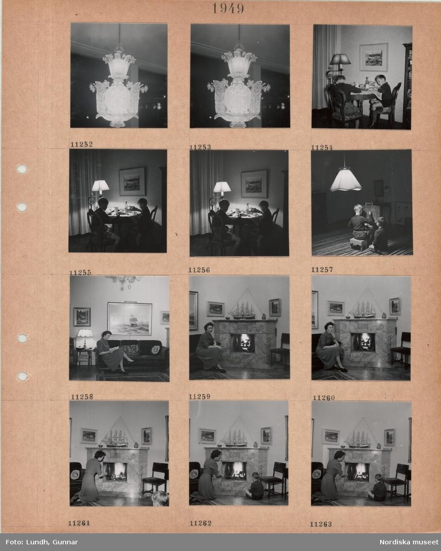 Motiv: Takbelysning med utsirad glaskupa, två pojkar sitter vid ett bord och målar med vattenfärg, två pojkar sitter på golvet, den ene ritar på en tavla på staffli, taklampa, kvinna i klänning sitter och läser en bok i en soffa, sitter vid en öppen spis med tänd brasa, båtmodell på spiselkransen, kvinna och pojke sitter framför en öppen spis med tänd brasa.