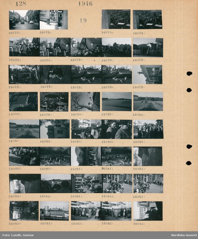 """Motiv: (ingen anteckning) ; Stadsvy med fotgängare och bilar.  Motiv: (ingen anteckning) ; En folksamling på en auktion, en man arbetar på ett tak på fotograf Peter P Lundhs fotoateljé, män sitter på trädgårdsmöbler och äter medhavd mat, landskapsvy med väg och träd, landskapsvy med åker, en man med två kor på en åker, en auktionsutropare, människor på en auktion, en folksamling utanför en byggnad med skylt """"Tullvisitation"""", bilar och människor på en bilfärja, en folksamling på kajen vid ett fartyg, stadsvy."""