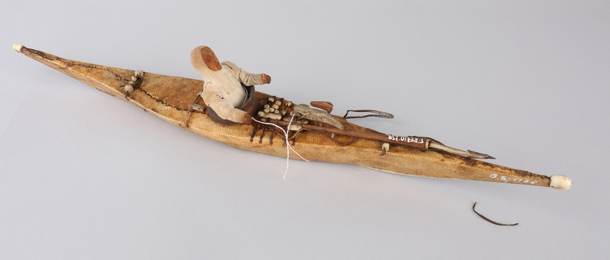 Harpun, del av fangstredskp som ligger på kajakkmodell med figur.