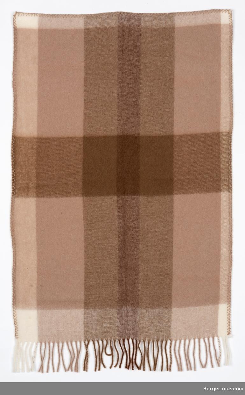 Lite teppe med storrutet mønster, frynser på den ene kortsiden