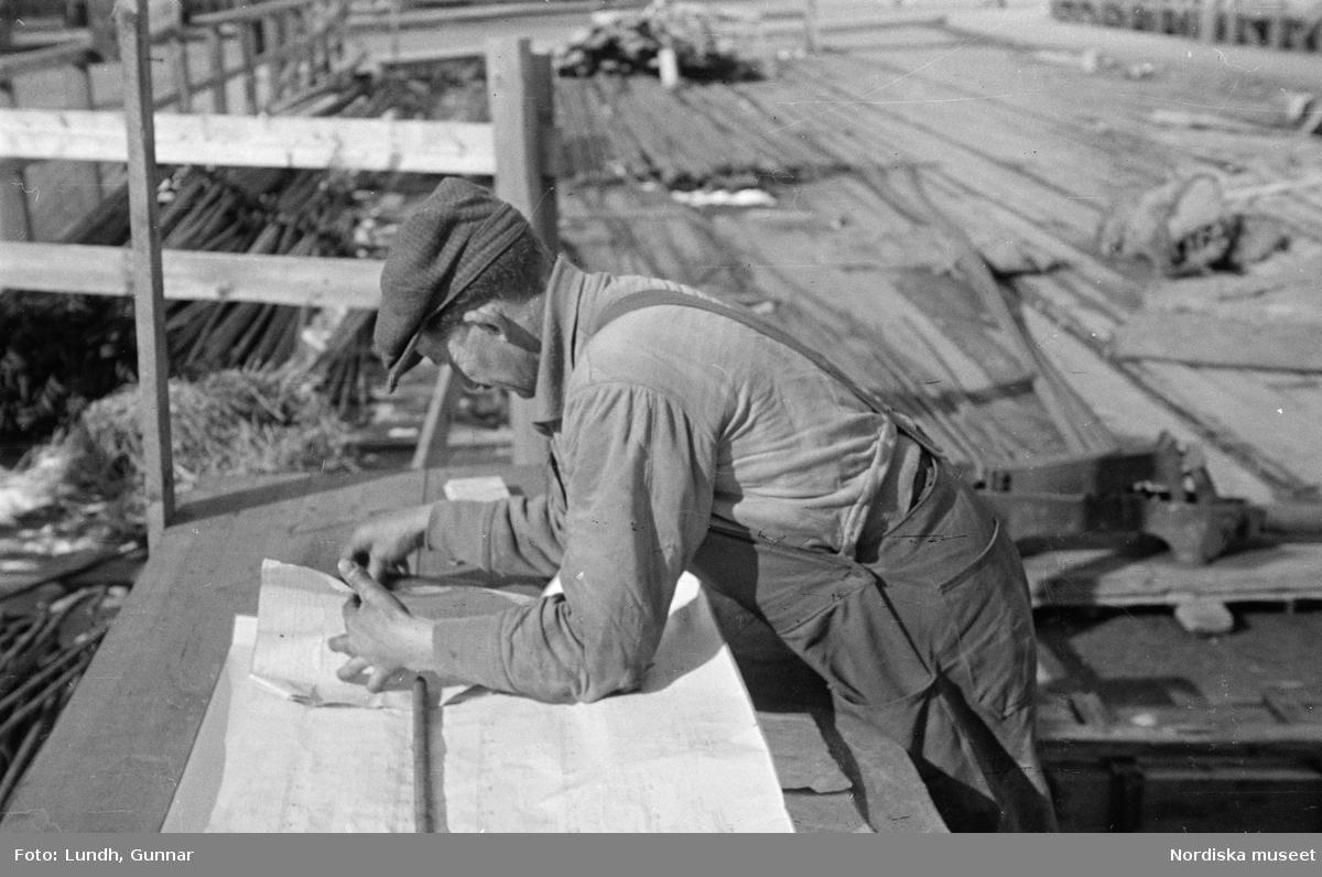 Stockholm, Slussen under byggnad. Byggnadsarbetare med ritning.