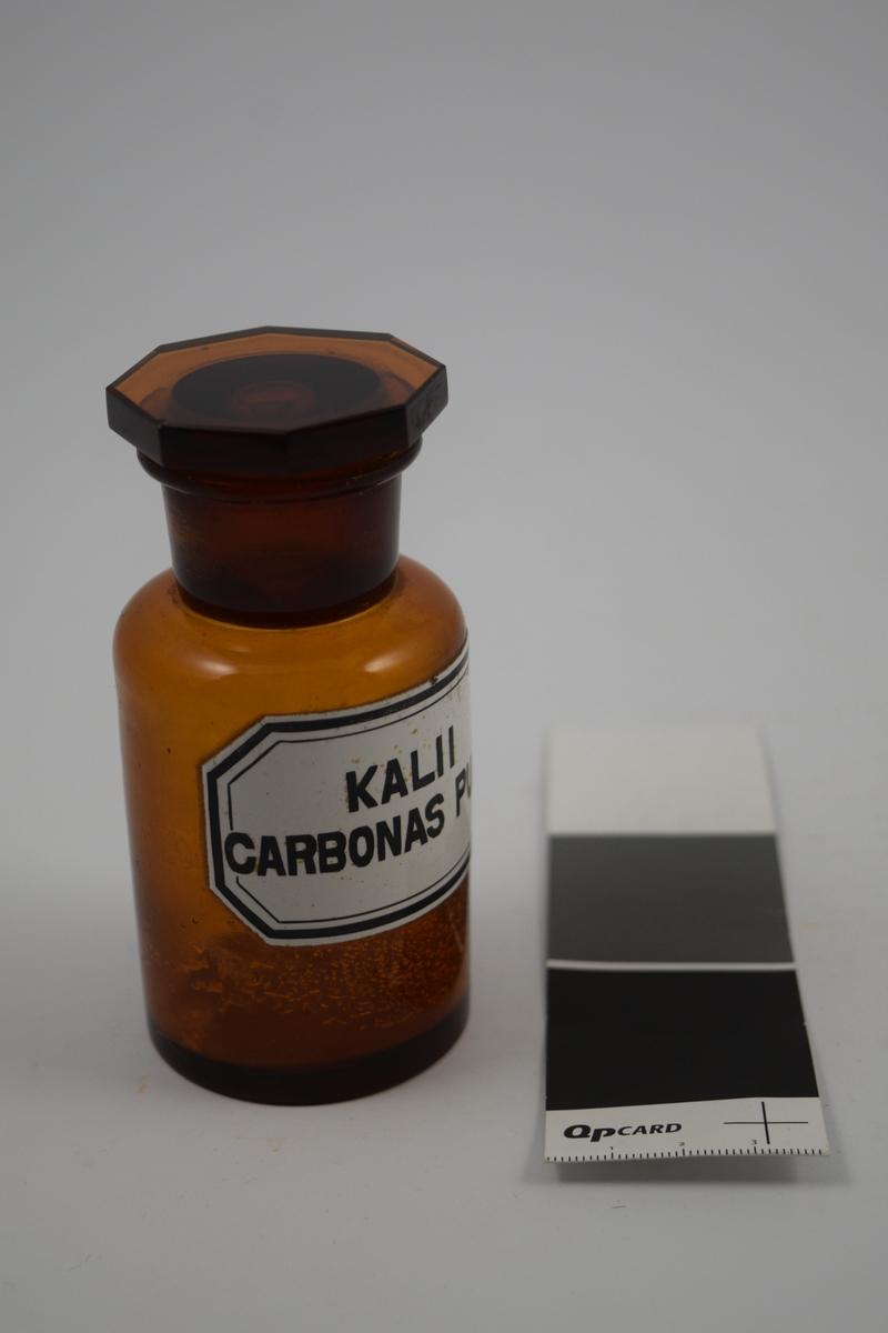 Brun glasskrukke med glasspropp. Kalii carbonas pulv. brukes til produksjon av legemidler.