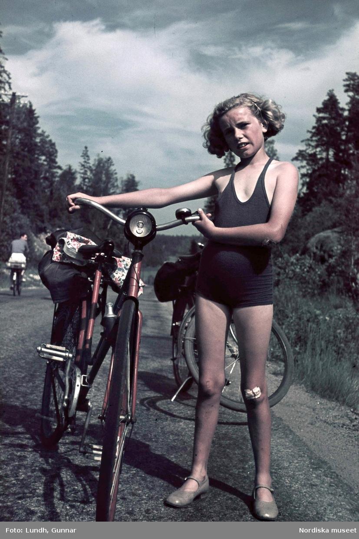 Flicka, fotografens dotter Jytte, i blå baddräkt med cykel. På vänster knä ett plåster.