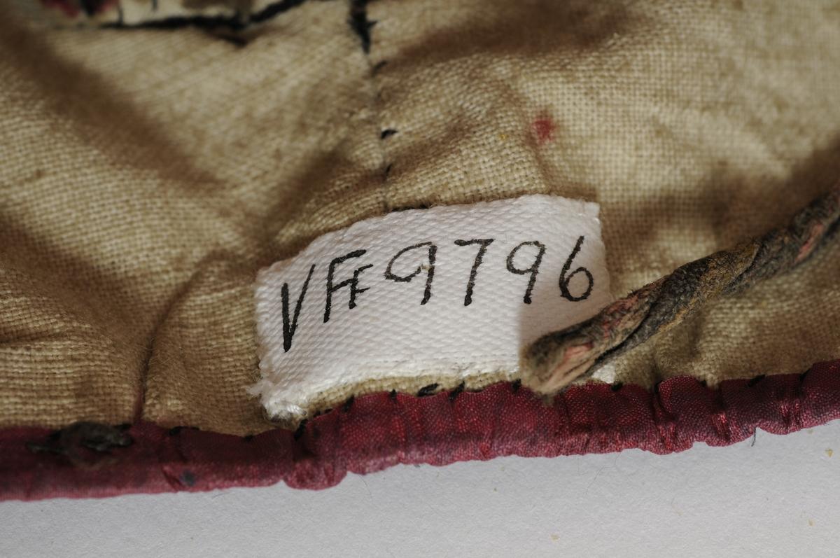 Svart silkelue med raud-lilla mønster.  Framme påsydd eit silkeband med legg. Kanta med silkeband nederst. Fora med ubleikt bomull. På kvar side påsydde turkise rosettar og tre små sløyfer midt oppe og på pullen.  To knyteband i bomull.