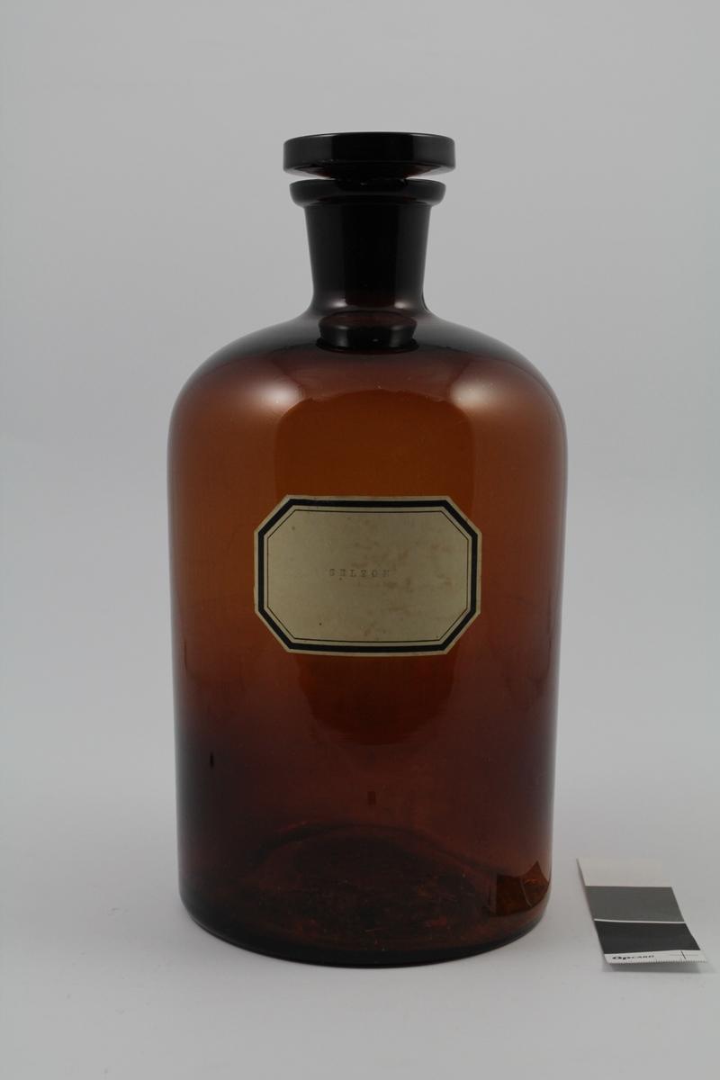 Brun glassflaske med smal hals, rommer 5 liter. Hvit merkelapp, sort skrift. Brukt til oppbevaring av løsninger.