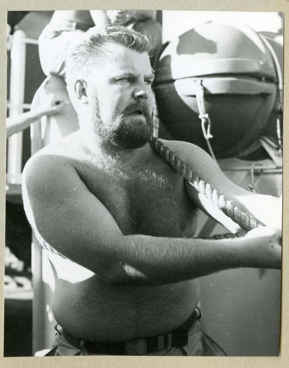 Bilden föreställer en besättningsman i fysiskt arbete ombord på minfartyget Älvsnabben under långresan 1966-1967.
