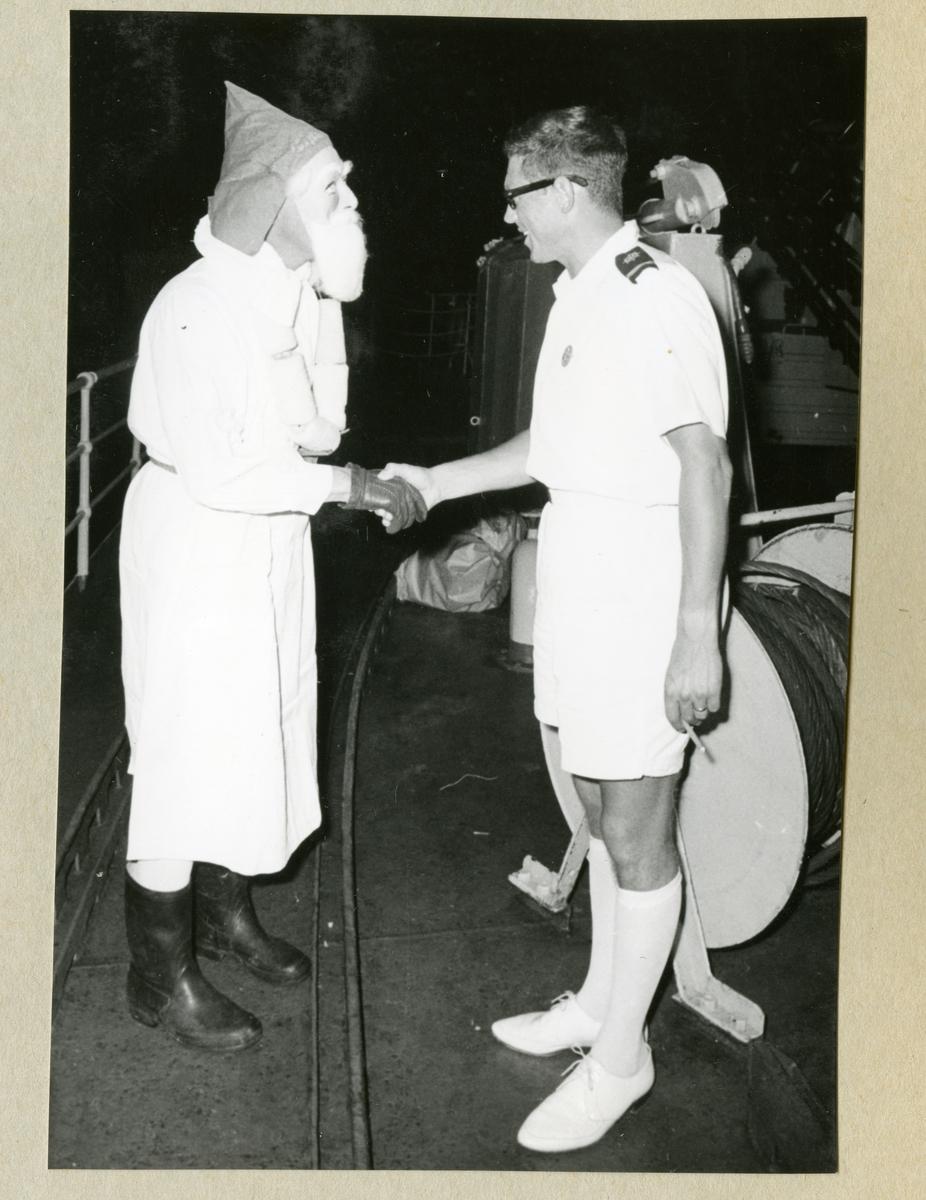 Bilden föreställer en besättningsmedlem iklädd sommaruniform som skakar hand med en man förklädd till jultomten. Bilden är tagen under minfartyget Älvsnabbens långresa 1966-1967 omkring jul.