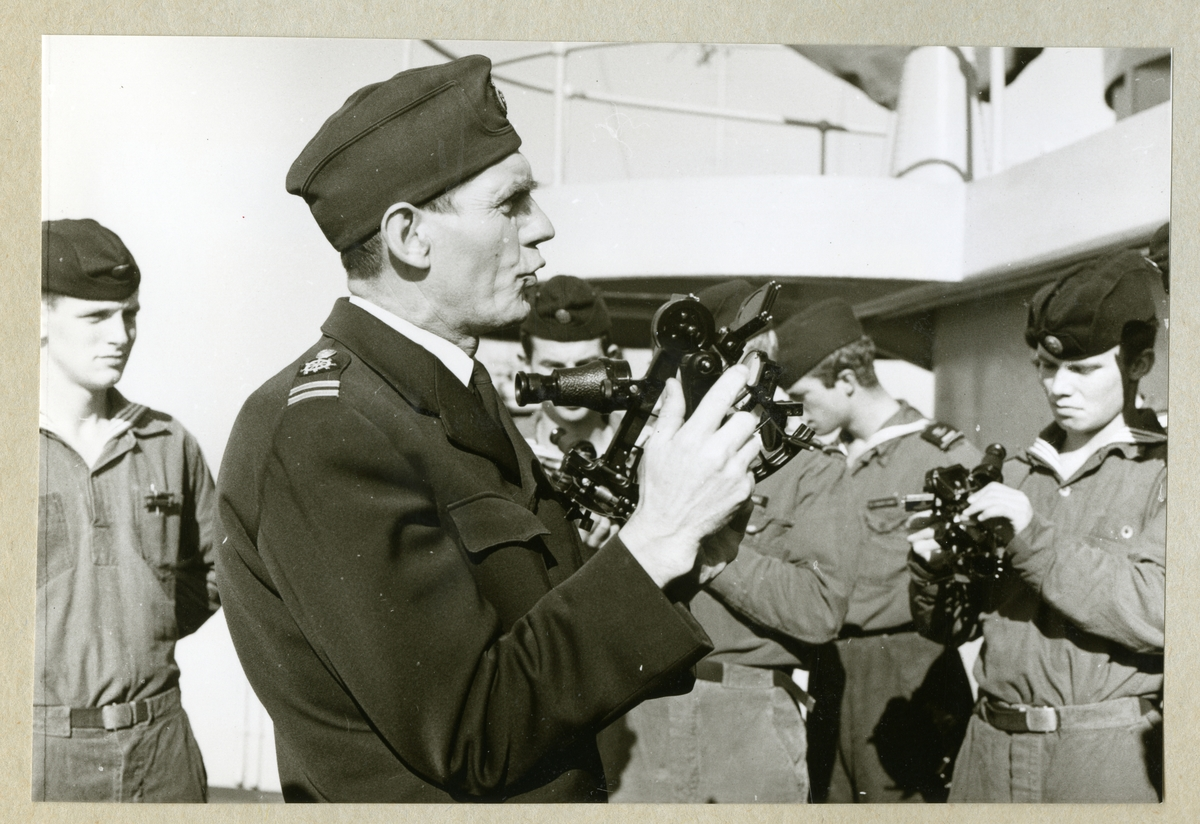 Bilden föreställer Oskar Linde, som instruerar en grupp av uniformsklädda besättningsmän ombord på minfartyget Älvsnabben i navigation med hjälp av en sextant. Bilden är tagen under långresan 1966-1967.
