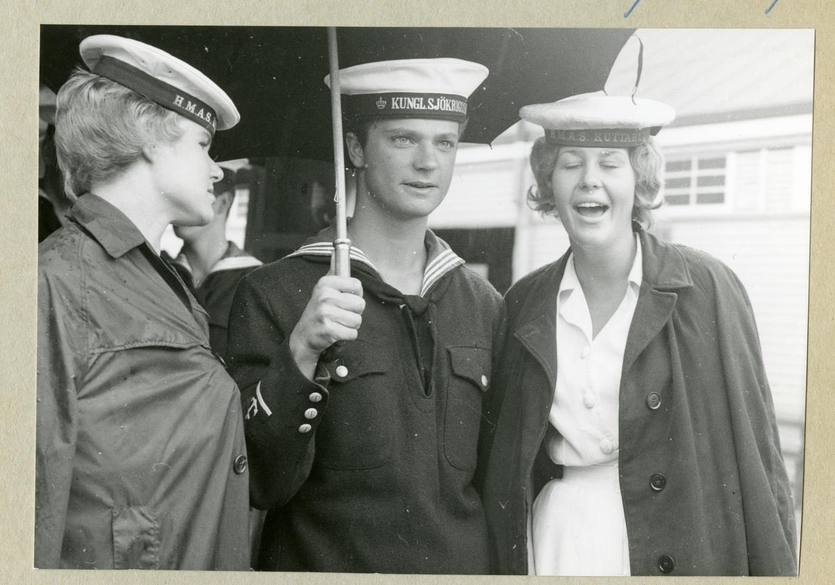 Bilden föreställer två kvinnor som står på varsin sida om kronprinsen Carl Gustaf, som är klädd i uniform och håller i ett paraply. De omgivande damerna är från HMAS Kuttaburra, en australisk marin utbildningsenhet. (HMAS = Her Majesty's Australian Ship).
