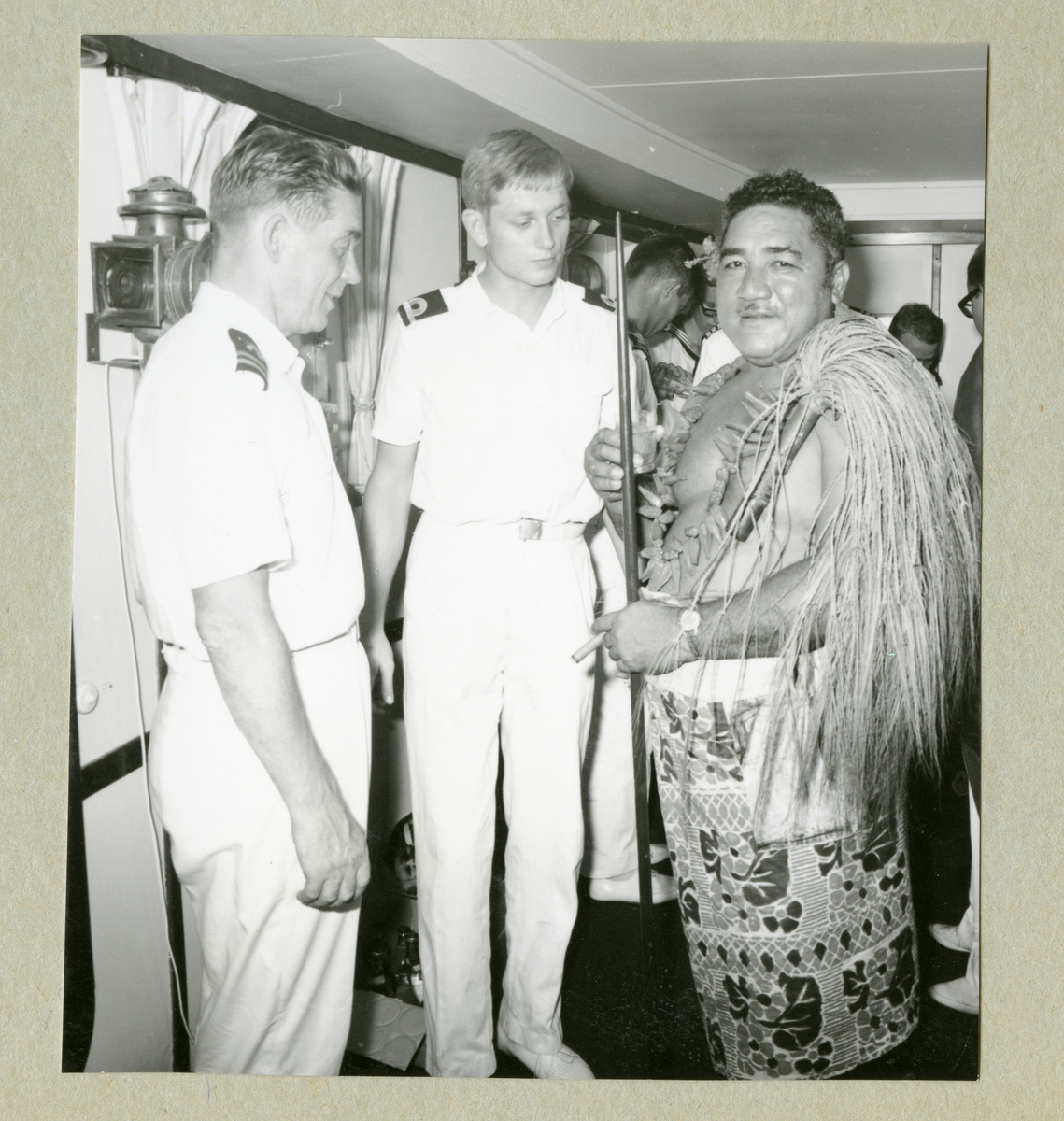 Bilden föreställer två besättningsmän i vita uniformer som står tillsammans med en man i lokala kläder. Bilden är tagen i Pago-Pago under minfartyget Älvsnabbens långresa 1966-1967.
